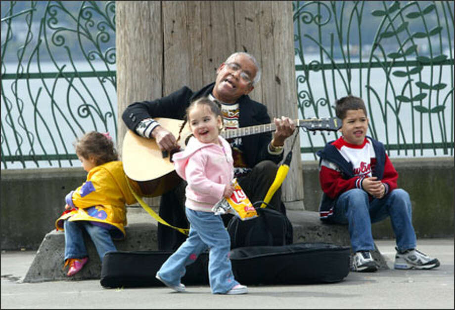 "Street musician Norm Lawrence entertains little tourists visiting Victor Steinbrueck Park in Seattle with ""Twinkle, Twinkle Little Star"" and ""I've Been Working on the Railroad."" The tunes made Tulima Pao Pao, 2, center, of Chicago dance along. Also entertained were her 2-year-old cousin Deanna Schweit of Lakewood and Tulima's 6-year-old brother, Mahzin Pao Pao. Photo: Karen Ducey, Seattle Post-Intelligencer / Seattle Post-Intelligencer"