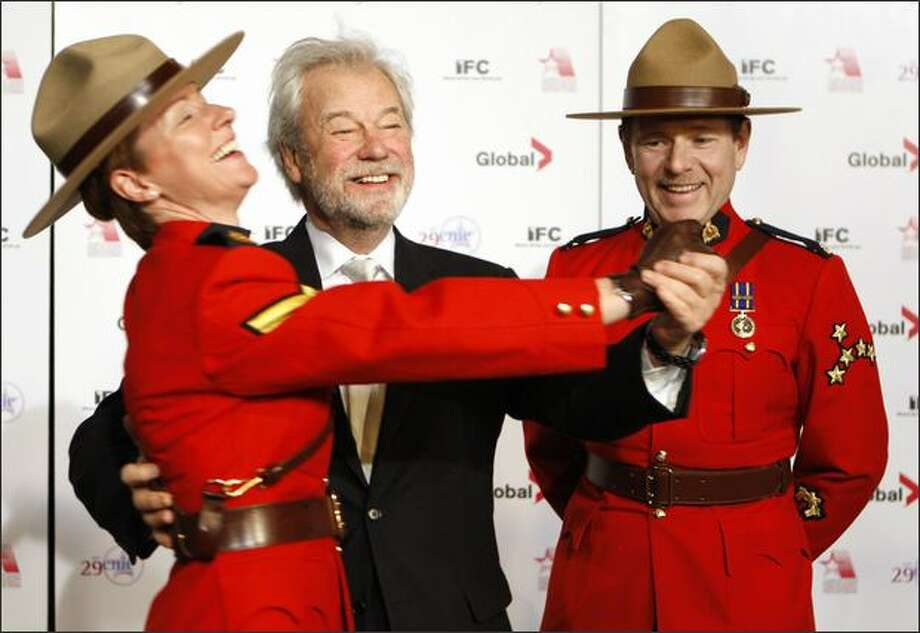 Canadian actor Gordon Pinsent, center, dances with Royal Canadian Mounted Police Cpl. Chrissie Lapointe, left,) as Constable Alexander Young watches on the red carpet at the 29th annual Genie Awards in Ottawa on Saturday. Photo: Reuters / Reuters