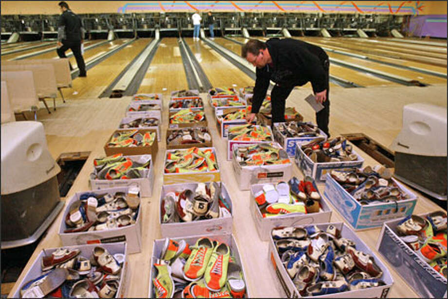 Willy Downs, manager of Hi-Line Lanes in Burien, looks over boxes of bowling rental shoes before a James G. Murphy auction at Leilani Lanes. In October 2005, the bowling alley was sold to a developer for $6.2 million. Open since 1961, it closed its doors in March 2006. Among the items auctioned were bowling lanes, pin-setting machines, balls, pins, fog machines, vending machines -- and even carved tikis. Photo: Grant M. Haller, Seattle Post-Intelligencer / Grant M. Haller