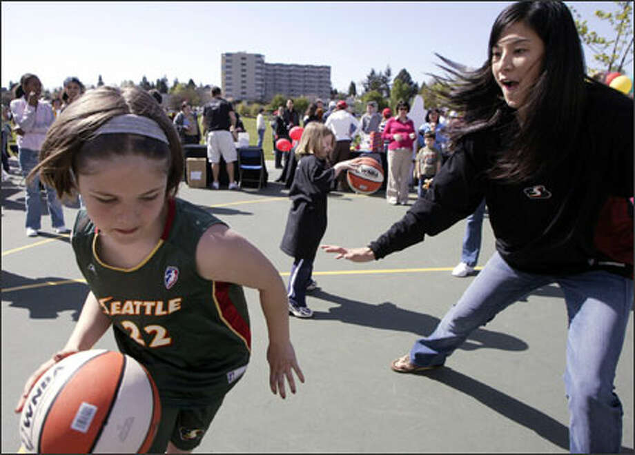 "Mariel Spencer, 9, tries to dribble past Seattle Storm player Lindsey Yamasaki on her way to the basket during ""Stormin' the Lake"" at the Green Lake Community Center. Fans turned out Sunday to learn team chants, have their faces painted, make locker-room signs and participate in basketball drills. Yamasaki has joined the Storm after stints with Miami, New York and San Antonio. During the opening address, Storm Coach Anne Donovan told the crowd, ""The Lord blessed us with the wonderful day to gather and have fun with the best fans in the world."" Photo: Jim Bryant, Seattle Post-Intelligencer / Seattle Post-Intelligencer"