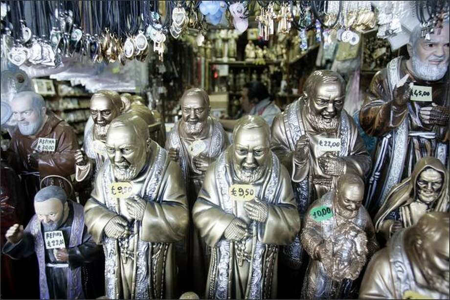 Statuettes and other souvenirs of Catholic Saint Padre Pio are shown for sale, at the monk's sanctuary in San Govanni Rotondo, southern Italy. The body of Padre Pio, a hugely popular Italian saint, will go on public display starting Thursday, with thousands expected to visit and pray to the mystic monk whom Catholic faithful believe bore the signs of Jesus' crucifixion. (AP Photo/Gregorio Borgia) Photo: Acclaimed Photography / Acclaimed Photography