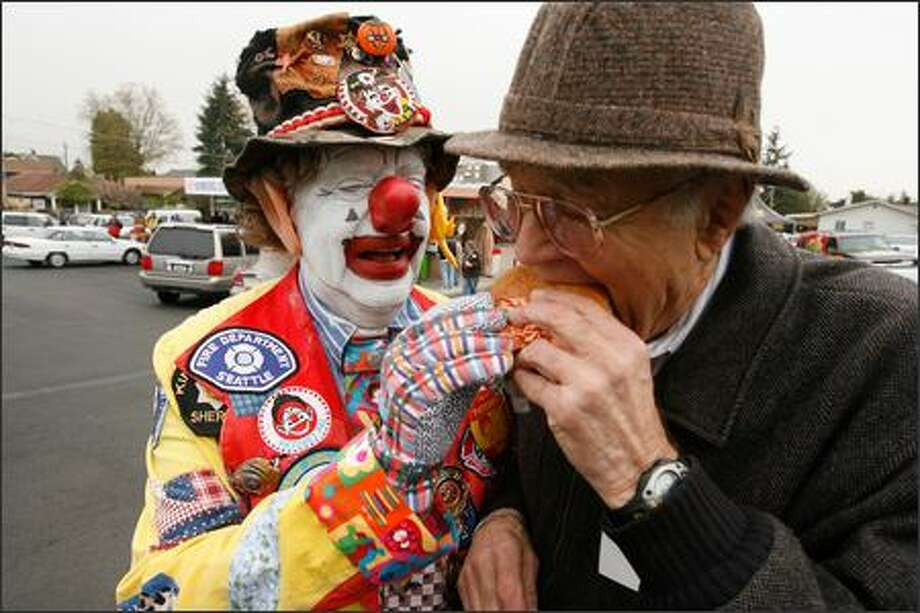 Old-time Seattle children's show host J.P. Patches (Chris Wedes), left, helps Dick Spady, co-founder and president of Dick's Drive-In Restaurants, sample a Deluxe Hamburger at the grand re-opening of the original Dick's drive-in at 111 N.E. 45th St. in Seattle, which opened in 1954.  Other Emerald City icons present included comedian John Keister and Bob Newman, J.P.'s sidekick and co-star, who played virtually every other character on his show during its later years. Photo: Grant M. Haller, Seattle Post-Intelligencer / Seattle Post-Intelligencer