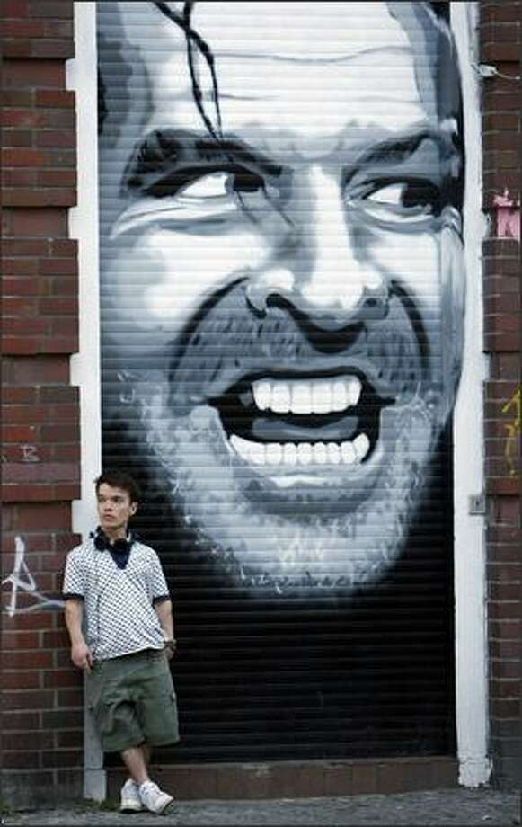 "A man stands next to graffiti commemorating Jack Nicolson's performance in ""The Shining"" in Kreuzberg, Germany. REUTERS/Pawel Kopczynski (GERMANY SOCIETY) Photo: Reuters / Reuters"