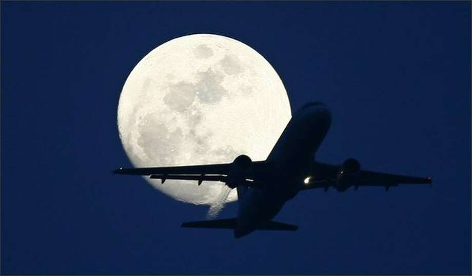 A passenger aircraft is silhouetted against the rising moon in New Delhi. Photo: Reuters / Reuters