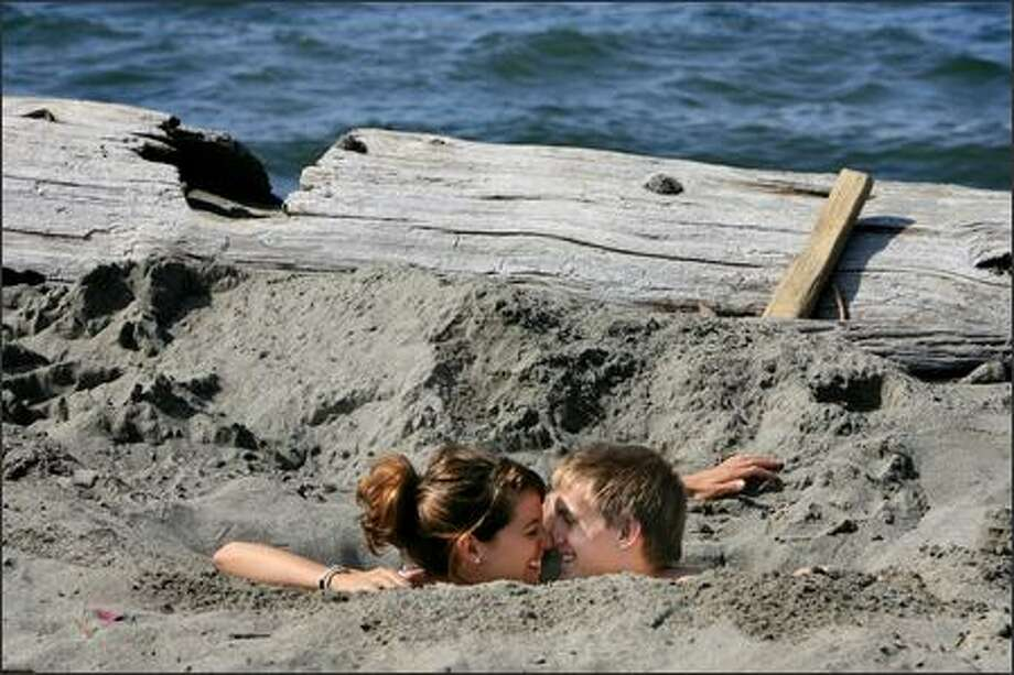 Sarah Vacanti of Seattle and Luke Golesh of Denver, both 20, enjoyed Monday's pleasant weather -- not to mention each other's company -- by digging a hole in the sand at Alki Beach Park in West Seattle. Both finished their sophomore year at Gonzaga University on Friday and decided to get an early start on summer. Photo: Dan DeLong, Seattle Post-Intelligencer / Seattle Post-Intelligencer