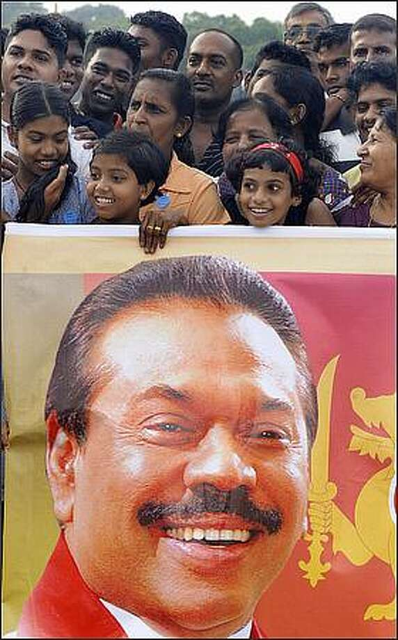 "Supporters hold a poster of Sri Lankan President Mahinda Rajapakse from Jordan as he returns to a hero's welcome in Colombo on Sunday. The president declared that the island's separatist Tamil Tiger rebels have been ""defeated militarily"" after decades of bitter ethnic bloodshed. Photo: Getty Images / Getty Images"