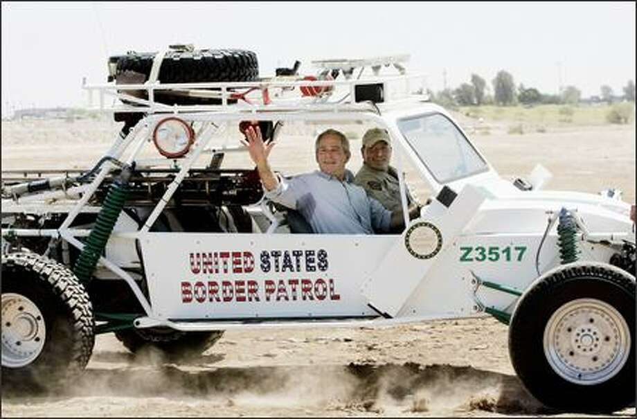 President Bush, left, waves as he rides a Dune Buggy driven by Rocky Kittle, right, as he tours the Yuma Sector Border along the U.S. Mexico International Border. Photo: AP Photo/WTJV-TV Via Miami Herald / AP Photo/WTJV-TV via Miami Herald