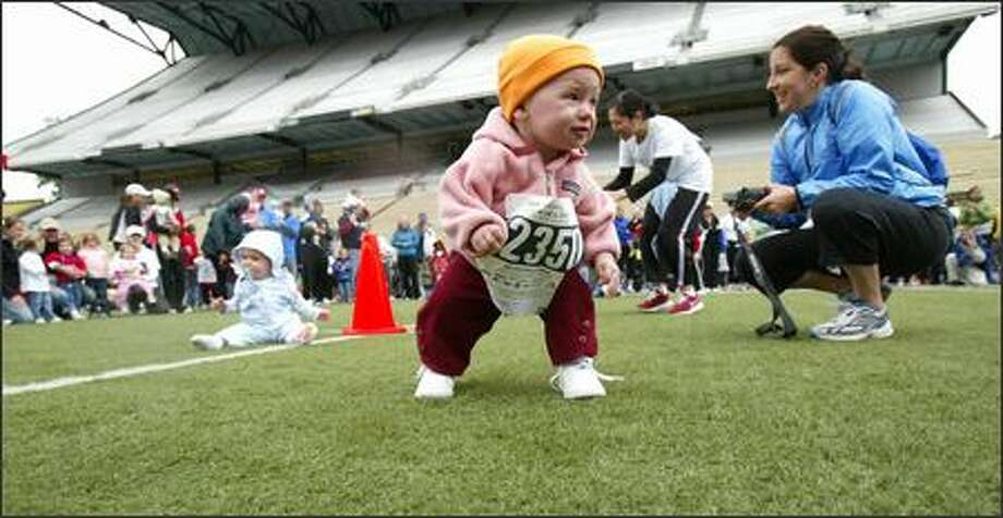 "Fierce and determined, a contestant heads across the field at Seattle's Husky Stadium during the ""Diaper Derby"" at the 25th Nordstrom ""Beat the Bridge to Beat Diabetes"" race.  The non-competitive event was open to all participants ages 3 and under. Photo: Karen Ducey, Seattle Post-Intelligencer / Seattle Post-Intelligencer"