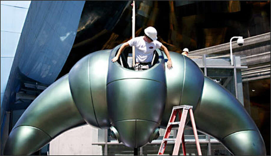 Luke Goldreyer with Scenario Design emerges from the inside of a new fiberglass icon as workers install the mysterious, unnamed thing at the Science Fiction Museum and Hall of Fame at the Seattle Center. Installers used a crane to lift the 16-foot-long, 3,000-pound icon and set it at the entrance to the museum Monday. The museum is set to open June 18. The museum would not elaborate on what the icon is, but would like Seattleites to decide. Is it an alien, a spacecraft, or is it something completely unknown? Photo: Gilbert W. Arias, Seattle Post-Intelligencer / Seattle Post-Intelligencer
