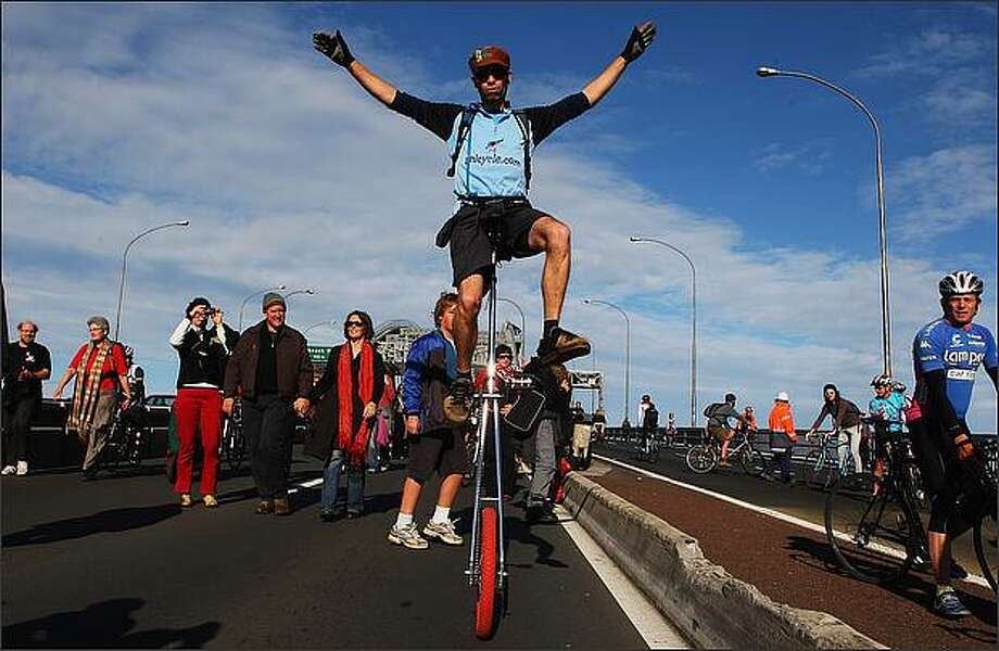 Protestor Tony Melton rides his unicycle across the Auckland Harbour Bridge to celebrate its 50th birthday and to also protest for better cyclist and pedestrian facilities Sunday in Auckland, New Zealand. Police were outnumbered and were powerless in their attempts to stop the protesters, who broke through the cordons and stormed onto the bridge causing northbound lanes to close for several hours. Photo: Getty Images / Getty Images
