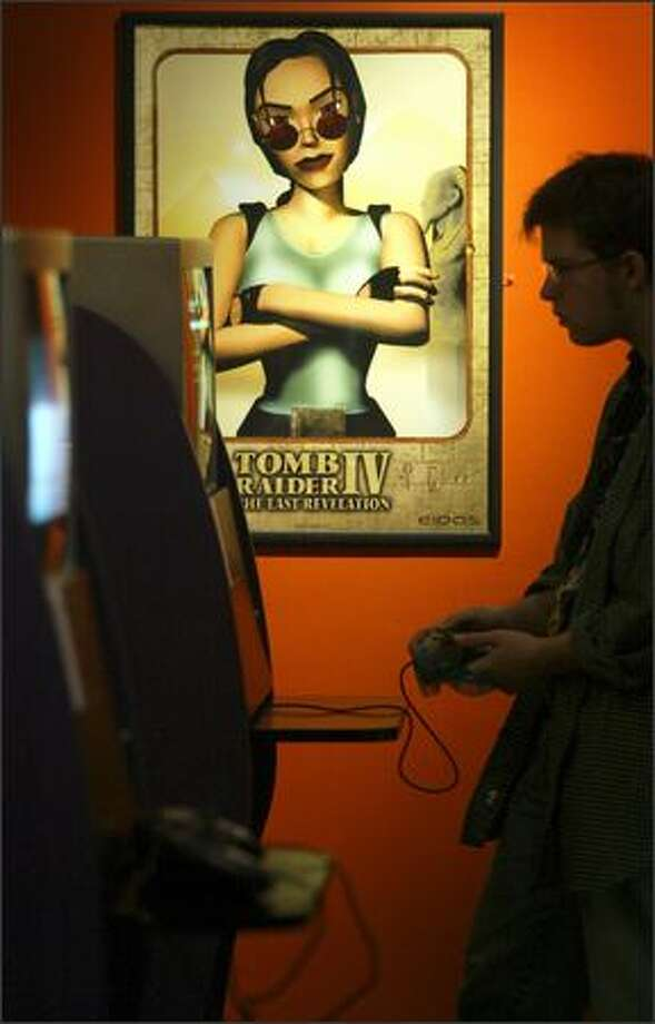 """Lara Croft of the """"Tomb Raider"""" video-game series keeps an eye on Pacific Science Center staffer Geoff Nunn as he plays one of the games during a preview Thursday of the exhibit """"Game On: The History, Culture and Future of Video Games."""" The exhibit runs through the end of August. Photo: Joshua Trujillo, Seattlepi.com / seattlepi.com"""