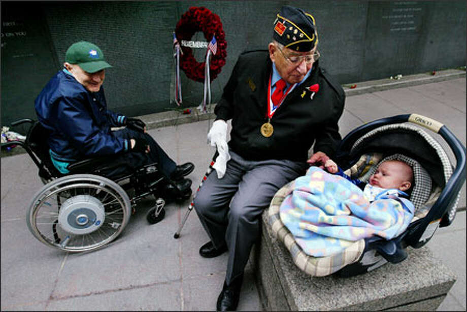 World War II veteran Joe Feldman makes friends with 3-month-old Nathan Lowe, while Vietnam veteran Jack Michaels watches at a Memorial Day service by the Garden of Remembrance wall at Benaroya Hall in Seattle. Nathan was named after his Marine father's friend, Lance Cpl. Nathan Wood, who was killed in Iraq in November. Wood's name was among those added to the wall. Photo: Paul Joseph Brown, Seattle Post-Intelligencer / Seattle Post-Intelligencer