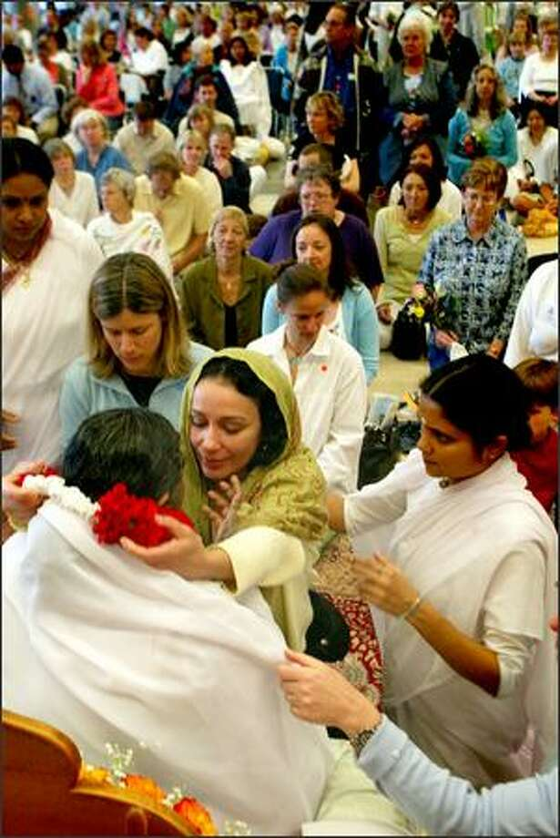 "Jyota Borges places a garland around Amma (""Mother""), an East Indian woman known as the ""hugging saint,"" at the Seattle Center, and receives a hug from her. Thousands of devotees waited in line Thursay for 15 to 30 seconds with Amma, who has wrapped her arms in an embrace around millions of people across the world while promoting peace and harmony. Photo: Karen Ducey, Seattle Post-Intelligencer / Seattle Post-Intelligencer"