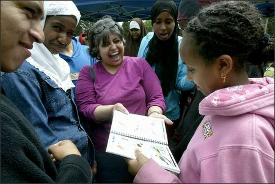 Irene Rodriguez, center, celebrates the first published work of Tigist Feseha, 11, right, as Feseha and fellow students from the Secondary Bilingual Orientation Center get their first look Sunday at the Seward Park Field Guide. Feseha drew a picture of a Western tanager for the guide, which was produced by students from area middle schools and the bilingual center.  The field guide they produced was unveiled at a community celebration Sunday at the Seattle park. Photo: Mike Urban, Seattle Post-Intelligencer / Seattle Post-Intelligencer