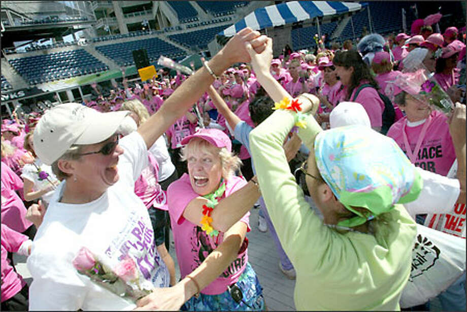 Trish Shands, center, of Seattle, a breast cancer survivor, dances with friends Margaret Nielsen, left, and Liz Westbrook in Seahawks Stadium after today's Race for the Cure. Photo: Karen Ducey, Seattle Post-Intelligencer / Seattle Post-Intelligencer