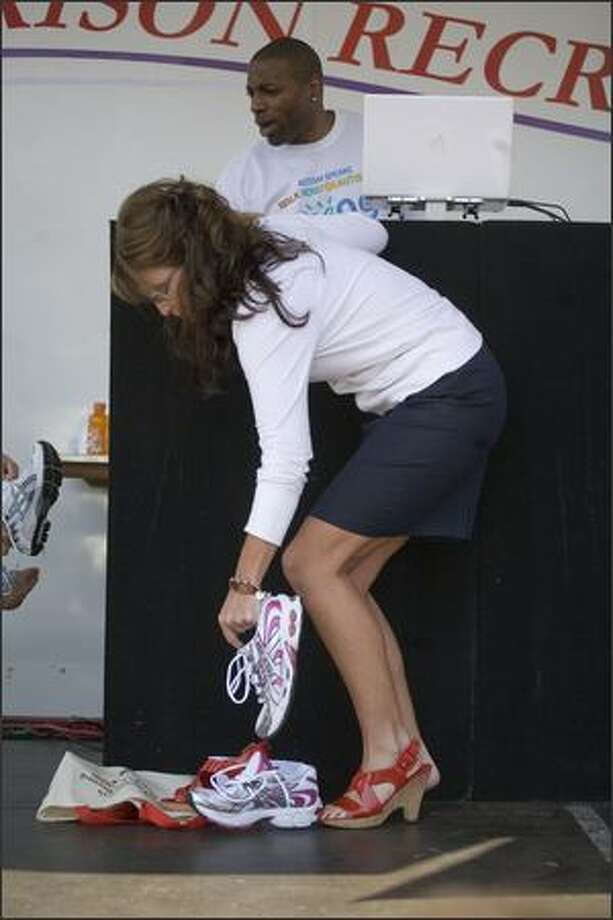 Alaska Governor and former Republican vice presidential candidate Sarah Palin changes into her walking shoes at an autism awareness walk and fundraiser sponsored by Autism Speaks at Manhattanville College on Sunday in Purchase, New York. According to Autism Speaks, the chance of being diagnosed with autism is 1 in 150. Photo: Getty Images / Getty Images