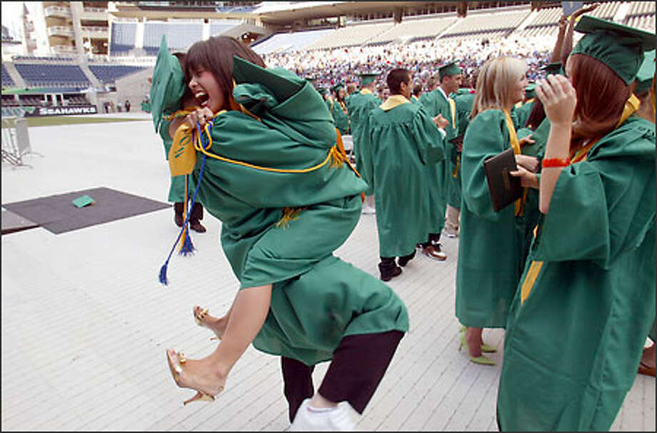 Roosevelt High School senior Maya Hatch leaps into the arms of her friend Malik Bates at the conclusion of commencement ceremonies at Seahawks Stadium. The ceremonies ushered in the start of area high school graduations. Photo: Mike Urban, Seattle Post-Intelligencer / Seattle Post-Intelligencer