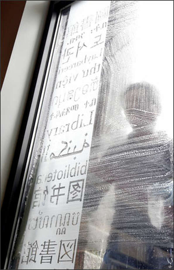 "The word ""library"" in various languages is imprinted on a window of the new International District/Chinatown branch of the Seattle Public Library at 713 Eighth Ave. S. Cleaning the window of the branch is Vien Nguyen. The new library will specialize in five languages: Chinese, Japanese, Korean, Tagalog and Vietnamese. Photo: Meryl Schenker, Seattle Post-Intelligencer / Seattle Post-Intelligencer"