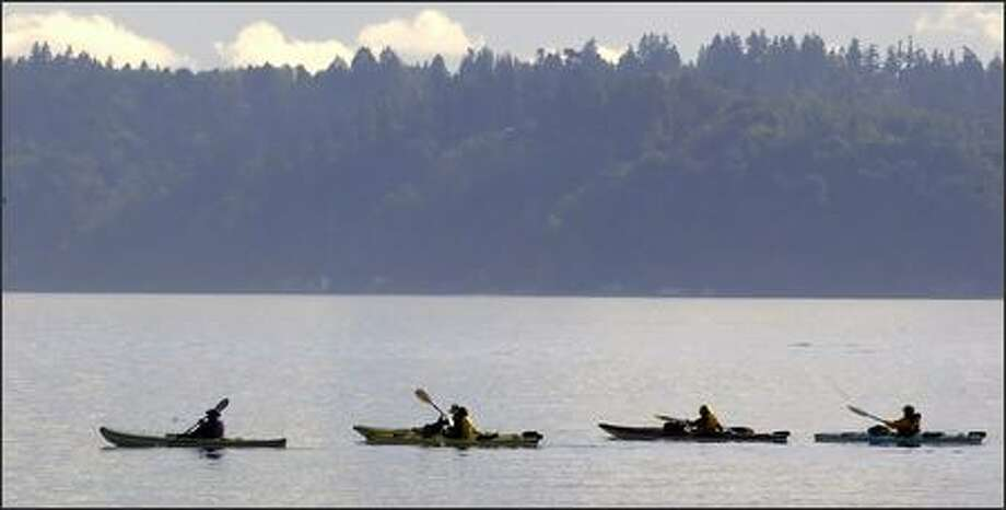 A group of kayakers paddles past Vashon Island on Friday after leaving Lincoln Park near the Washington State Ferries terminal at Fauntleroy. Photo: Jim Bryant, Seattle Post-Intelligencer / Seattle Post-Intelligencer