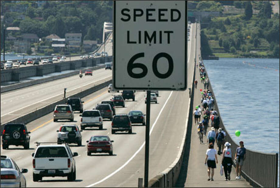 Area Christians cross the Interstate 90 bridge Sunday while participating in CrossWalk America. The movement is a national effort to show Christian alternatives to America's religious right. Photo: Mike Kane, Seattle Post-Intelligencer / SEATTLE POST-INTELLIGENCER
