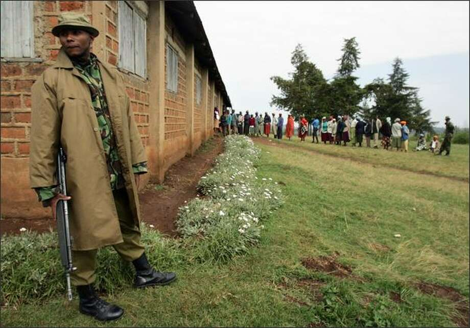 A Kenyan policeman (L) patrols the perimeter of a local polling station in the western Kenyan town of Olmelil during one of the five by-elections being held in the country. Photo: Getty Images / Getty Images