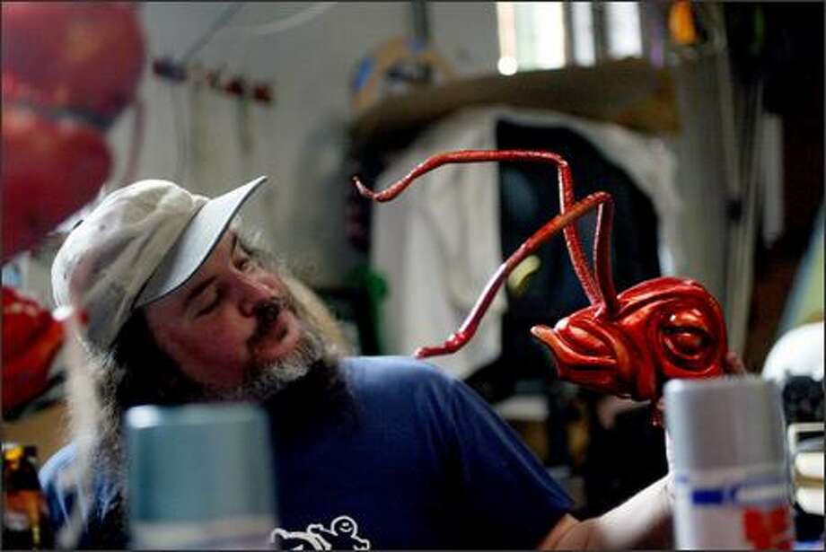 """Rob D'Arc works on his """"Insects of Mass Destruction"""" on Monday for the Fremont Solstice Parade. Each insect will have four arms and two legs and carry rifles. Four coats of paint in colors such as copper and candy-apple red will cover each creature. Volunteers are needed all week to help paint and build the many elaborate floats that will be participating in Saturday's parade, which will begin at noon. For more information, call 206-547-7440 or check out www.fremontartscouncil.org. Photo: Karen Ducey, Seattle Post-Intelligencer / Seattle Post-Intelligencer"""