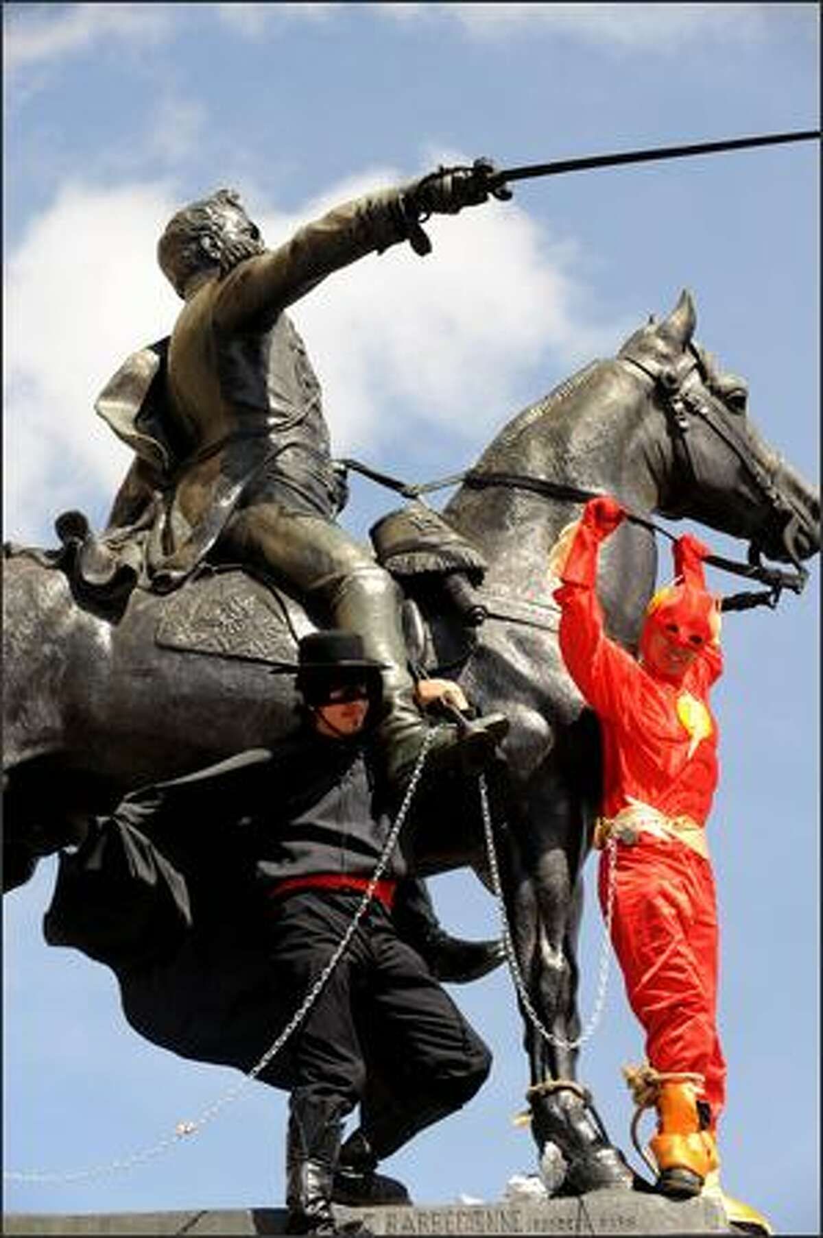 Two separated fathers dressed up as Zorro (L) and Flash remain chained to the Simon Bolivar statue during a protest to demand a shared custody of their children on Friday in Bogota, Colombia.