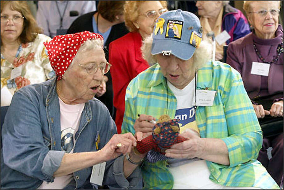 Elana Larson, right, signs a Rosie the Riveter teddy bear with Margaret Berry at the opening of Rosie's Diner, a new, state-of-the-art dining facility for Boeing Co. employees in Renton. Berry worked at Boeing during the World War II, when thousands of women entered the U.S. work force. Larson worked at the Keyport Navy base during the war. Photo: Phil H. Webber, Seattle Post-Intelligencer / Seattle Post-Intelligencer