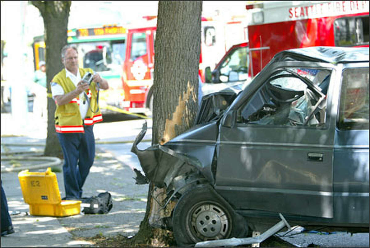 A crash investigator snaps photographs at the scene where a van crashed into a tree near South Lake Union in Seattle. The seven people riding inside were injured, four of them critically.