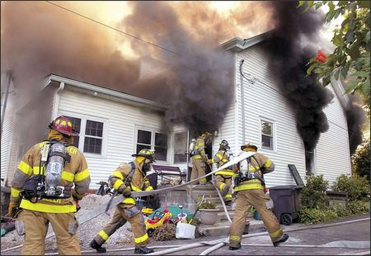 Winchester firefighters battle a fire at a home in Winchester, Ky., on Tuesday. The fire caused heavy fire damage to the basement and first floor of the home. The second floor of the 109 year-old home sustained smoke damage. The cause of the fire was under investigation. (AP Photo/The Winchester Sun, James Mann)