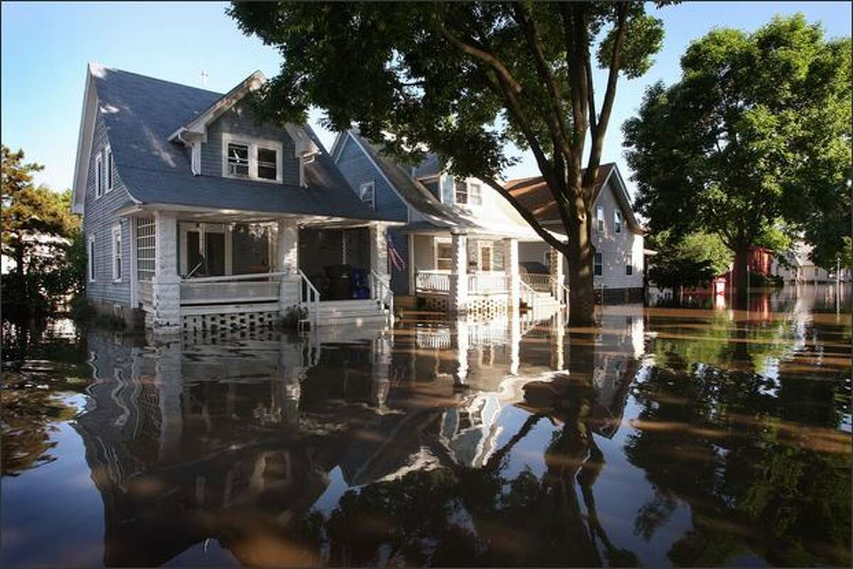 Water levels drop around homes in a southwest neighborhood in Cedar Rapids, Iowa. Flood water from the Cedar River began receding in the city today after cresting at over 30 feet.