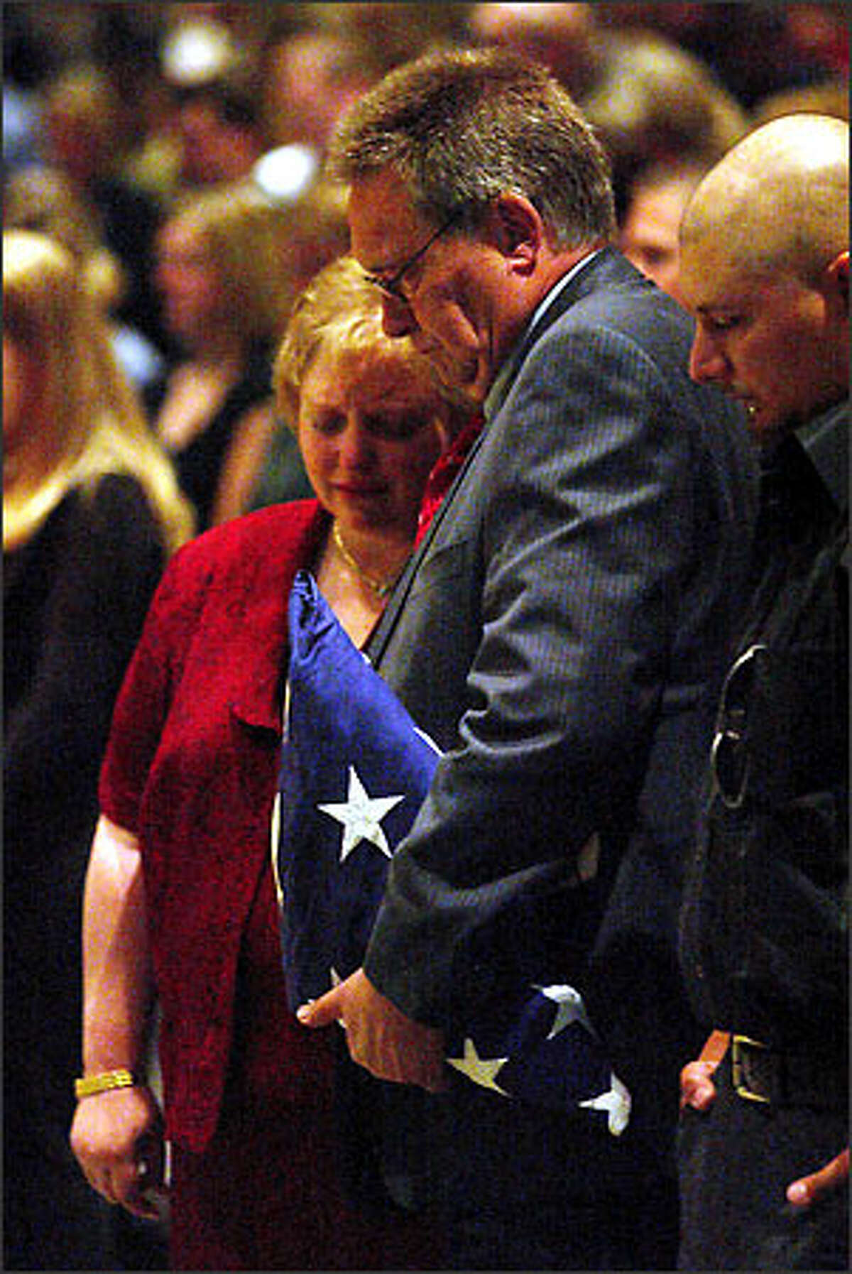 At a memorial service in Everett, David Calavan of Stanwood holds the flag that covered the grave of his son, Marine Pfc. Cody Calavan, who was killed May 29 while serving in Iraq. At left is Cody's stepmother, Pamela Calavan. Cody Calavan's name will be engraved on Stanwood's war memorial.