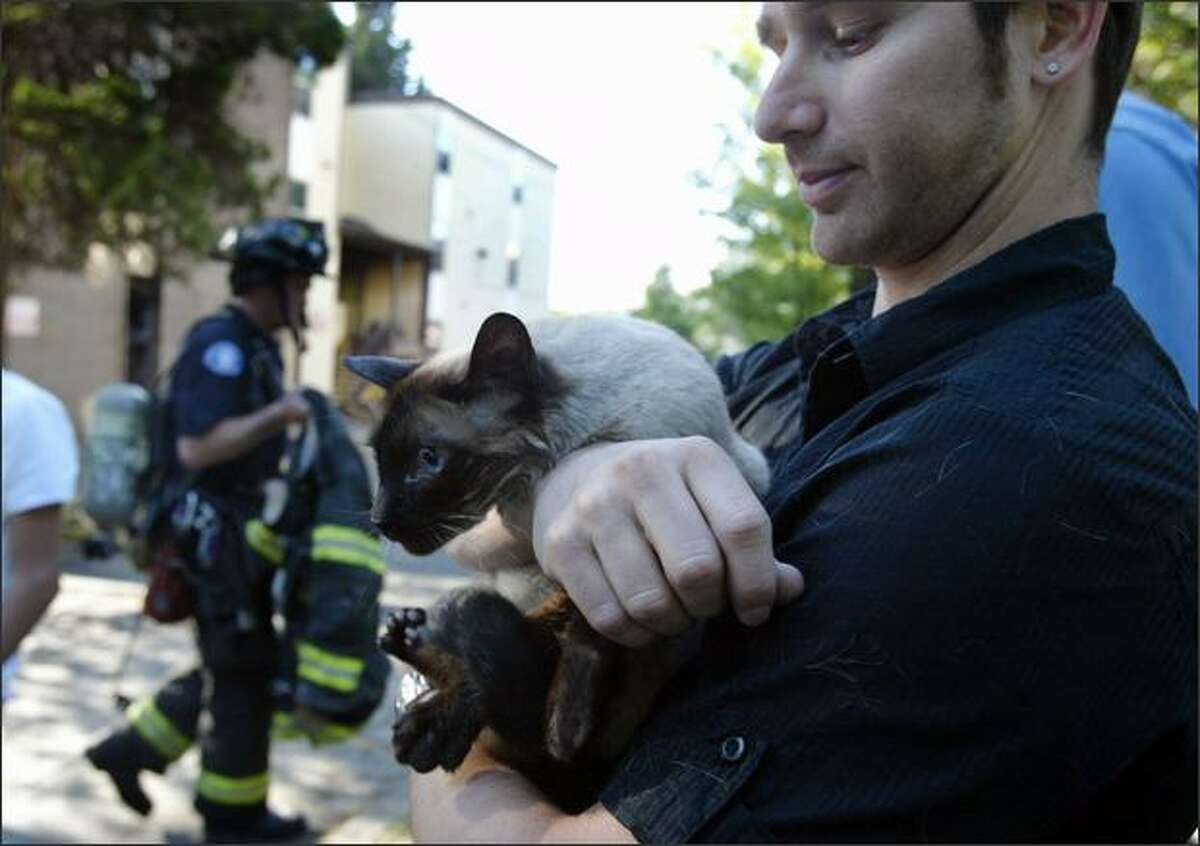 Gil Zalmanovitch holds his cat Ushu who was rescued from Zalmanovitch's apartment after a fire destroyed three apartments at the corner of Roanoke St and Eastlake Ave E in Seattle. Zalmanovitch, was not home at the time of the fire.