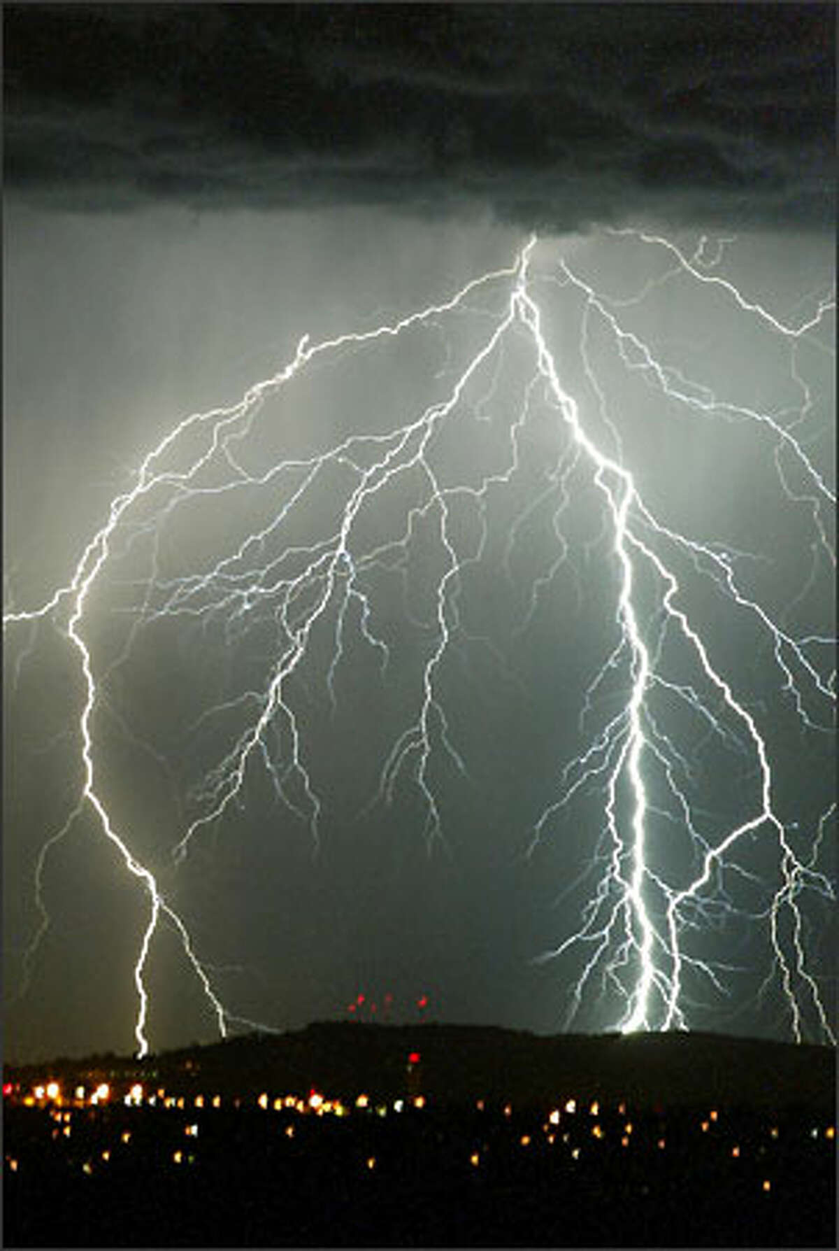Lightning strikes the Cascade foothills as seen from Inspiration Point on Vashon Island.
