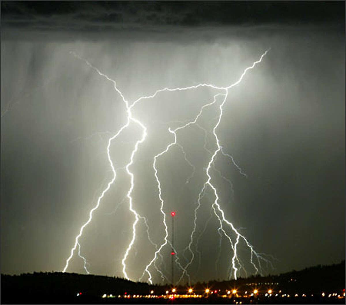 Lightning strikes the Cascade foothills as seen from Vashon Island.