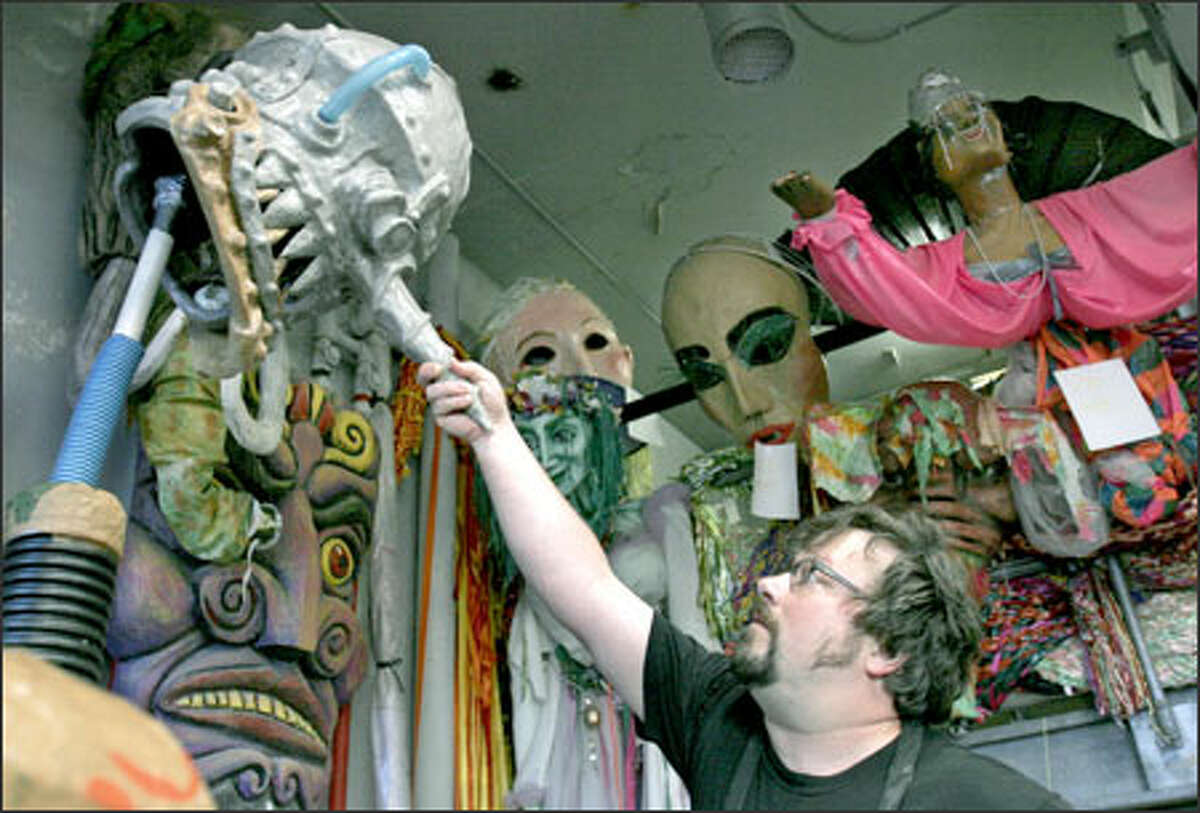 Brian Kooser, a Seattle puppet designer, puts the head on Mark II, a giant puppet he created for the Fremont Arts Council's Solstice Parade. The event is one of the highlights of the 34th Fremont Fair.
