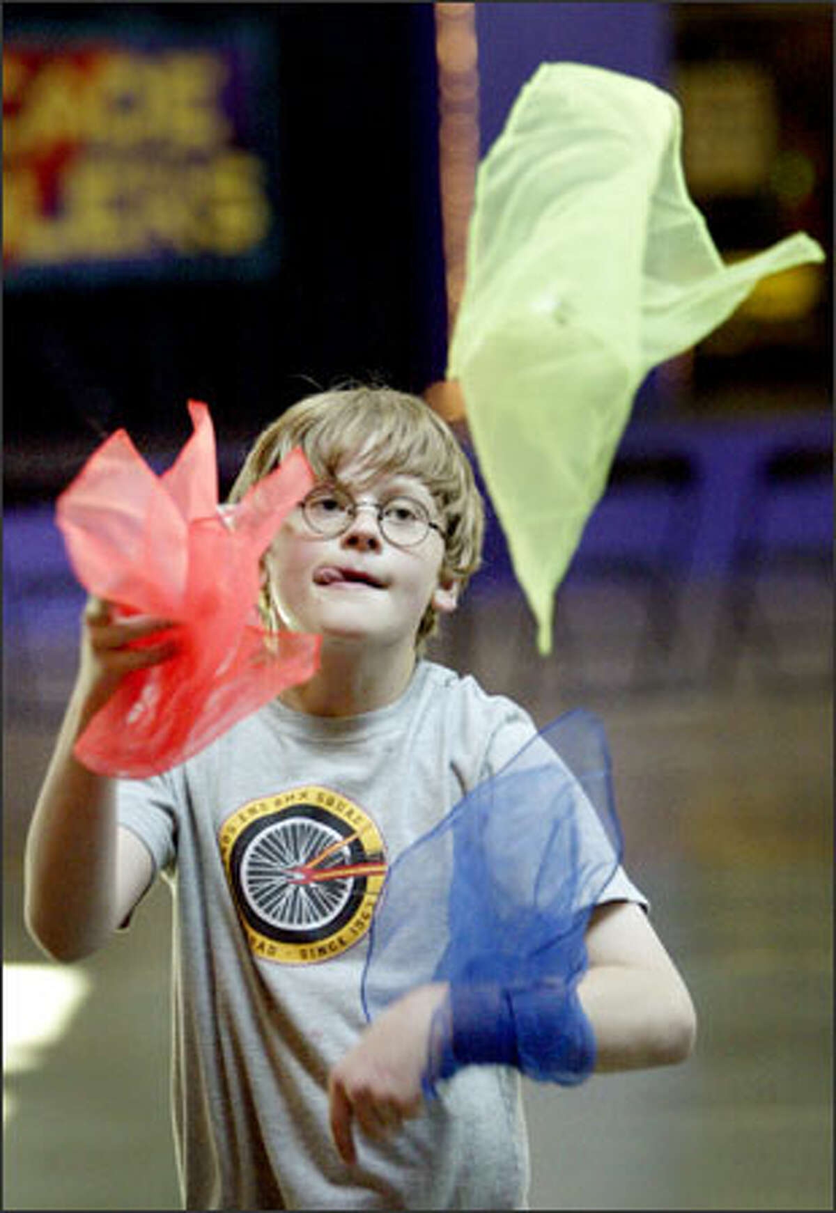 Ten-year-old Benjamin Groth of Minneapolis gets a free lesson at the Seattle International Juggling Festival in the Seattle Center's Center House. The Cascade Jugglers Club sponsored the free festival.