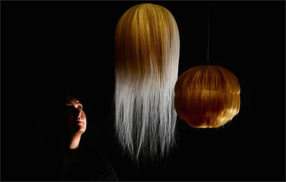 Claire Neil looks at a series of Japanese lanterns made from hair, by fashion designer Kosuke Tsmura, which is part of an exhibition at The Lighthouse on Tuesday in Glasgow, Scotland. Haptic, is an exhibition from the Nippon Design Museum, Tokyo, and gets its only Scottish showing at The Lighthouse from 18 June 2008. Photo: Getty Images / Getty Images