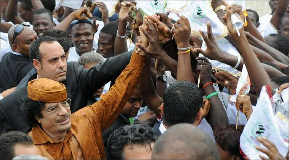 A cheering crowd tries to touch the hands of Libyan leader Moamer Kadhafi as he arrives to attend the opening session of the 10th summit of Community of Sahel-Saharan States in Cotonou on Tuesday. The two-day 10th summit of Heads of State of the Community of Sahel-Saharan States (CEN-SAD) has commenced in the Benin Republic. According to CEN-SAD, the organisation is the biggest economic community in Africa, with an estimated 411.2 million people, representing nearly half of the continent's population.