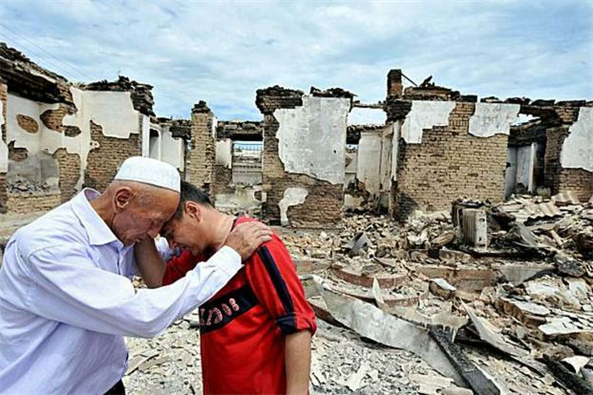 After the terror: Ethnic Uzbek men shed tears near a destroyed house in the Kyrgyz village of Shark near Osh. The first airlifts of aid arrived for tens of thousands who have fled deadly ethnic bloodletting and mass rape in Kyrgyzstan.