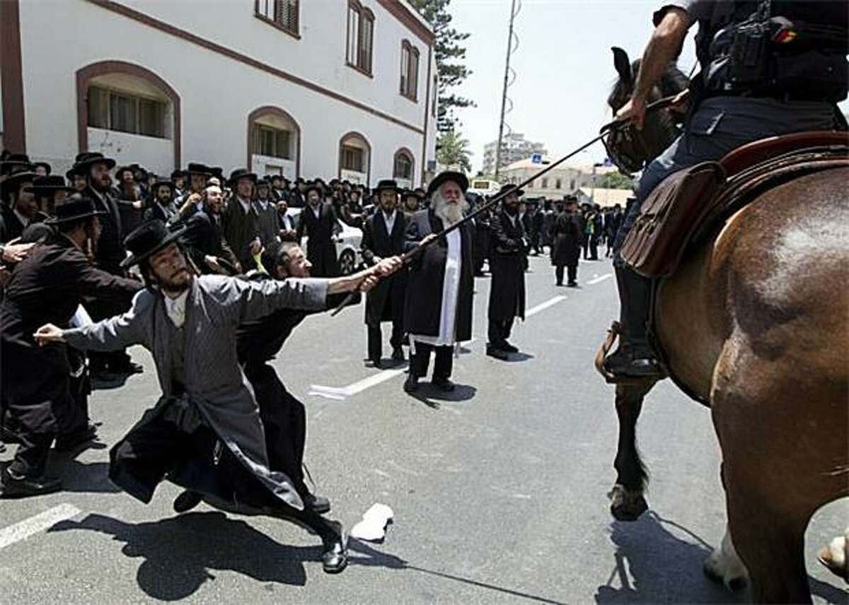 Defenders of the dead: Anti-Zionist, Ultra-Orthodox Jews grab a mounted policeman's whip during a clash over the removal of ancient tombs in Jaffa, Israel. Construction is scheduled for a site that the Ultra-Orthodox men say contains historic Jewish graves.
