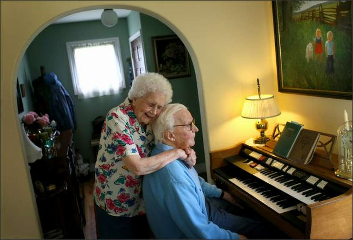 Sylvia Jones embraces her husband Harold after he played a song in their home in Bellingham. The long-time Seattle-area residents, who have relocated to Bellingham, have been married for 70 years.