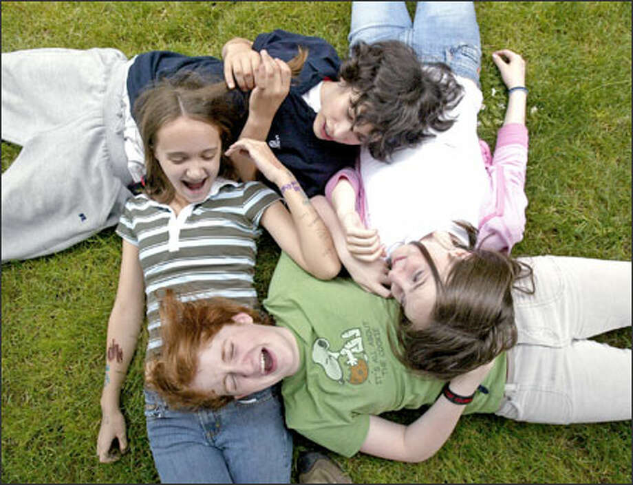 Clockwise from left, friends and seventh-graders Samantha Wennerlind, Leo Friedman, Kate Collins and Rose McCarty enjoy the first day of summer after their last day of school at Washington Middle School. The foursome was relaxing on the front lawn of Stevens Elementary, where they were watching a kickball game. Photo: Dan DeLong, Seattle Post-Intelligencer / Seattle Post-Intelligencer