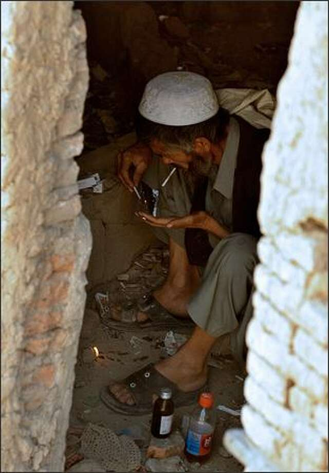 An Afghan drug addict smokes heroin in an abandoned building in Kabul. Photo: Getty Images / Getty Images