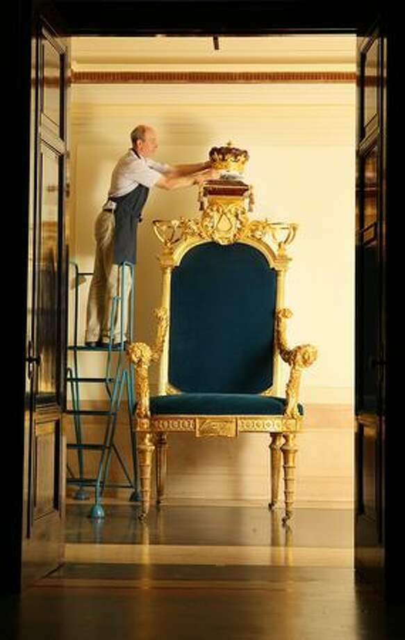Restorer Ray Dudman fits the crown to a ceremonial throne made for the Prince of Wales (later King George IV) in 1790 at the Library and Museum of Freemasonry on Tuesday in London. The Throne and two Wardens chairs in gilded limewood have been restored at a cost of £100,000 and will form part of the Freemasonry and the French Revolution Exhibition which runs from July 1 to December 18, 2009 at the Freemason's Hall. (Photo by Peter Macdiarmid/Getty Images) Photo: George Vetter / George Vetter