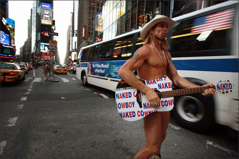 The street performer Robert Burck, who is known as the Naked Cowboy, performs for pedestrians Tuesday in Times Square in New York City. The $6-million lawsuit filed by the Burck against M&Ms candy maker Mars Incorporated can go forward on grounds of trademark infringement a New York judge has ruled. Burck filed the suit about video billboards depicting a blue M&M dressed in his signature outfit in an animated cartoon it ran on two video billboards in Times Square. Photo: Getty Images / Getty Images