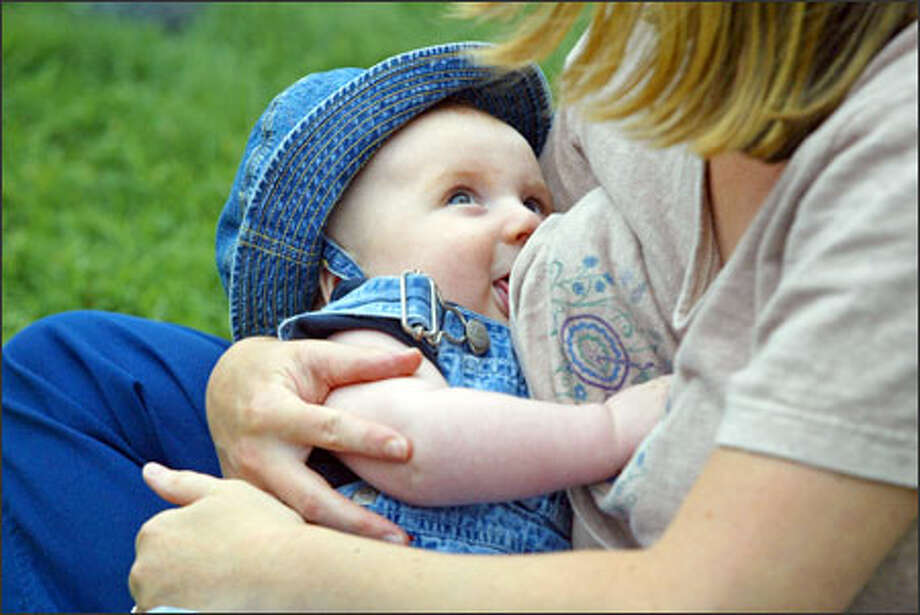 Lori Mudge of Seattle breast-feeds son Julian Mudge-Burns at a Seattle Center rally staged to make a point: It is hip to NIP -- Nurse In Public. Photo: Meryl Schenker, Seattle Post-Intelligencer / Seattle Post-Intelligencer