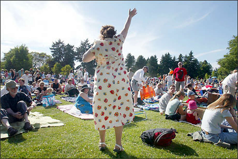 Kathryn Minturn of Ballard stakes a claim to a patch of grass and tries to capture the attention of her friends at the ZooTunes concert at Woodland Park Zoo. Photo: Mike Urban, Seattle Post-Intelligencer / Seattle Post-Intelligencer