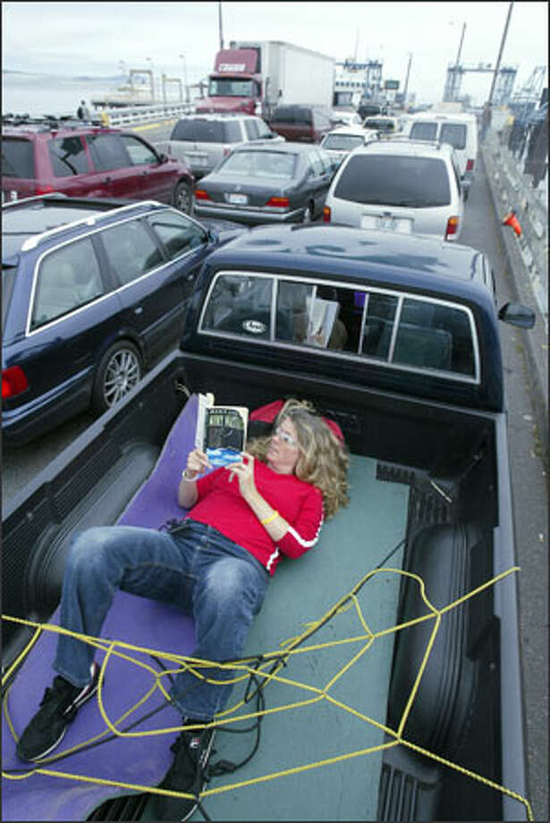 Kari Richards of Seattle relaxes in the back of her friend Kim Buchanan's pickup while waiting for a ferry from Vashon Island. Richards attended Buchanan's birthday party Wednesday night on the island. Photo: Mike Urban, Seattle Post-Intelligencer / Seattle Post-Intelligencer