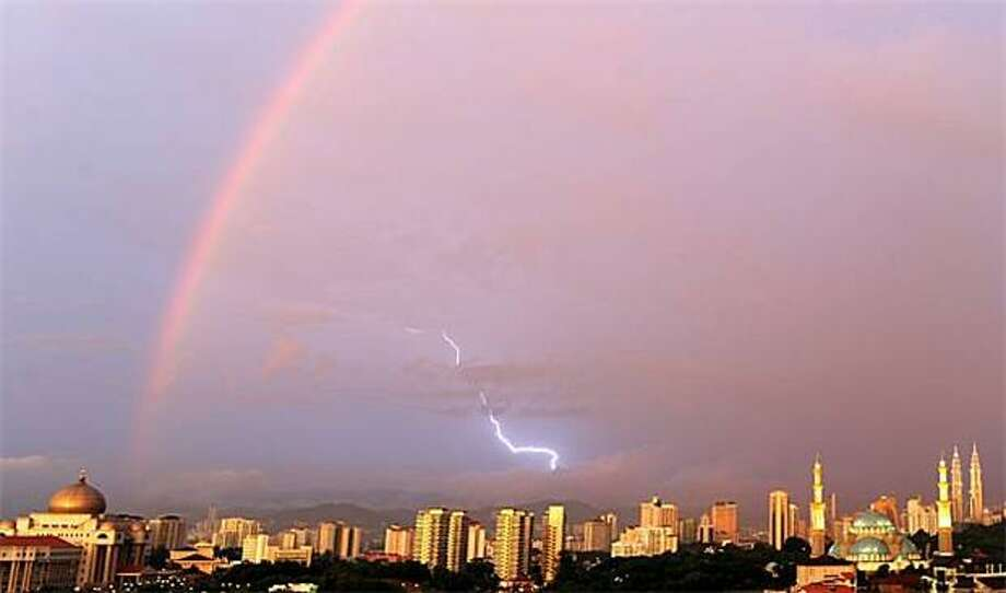 A meteorological trifecta:A rainbow, a lightning strike and the sunset occur simultaneously over the Kuala Lumpur skyline. Photo: Saeed Khan, AFP / Getty Images / AFP / Getty Images